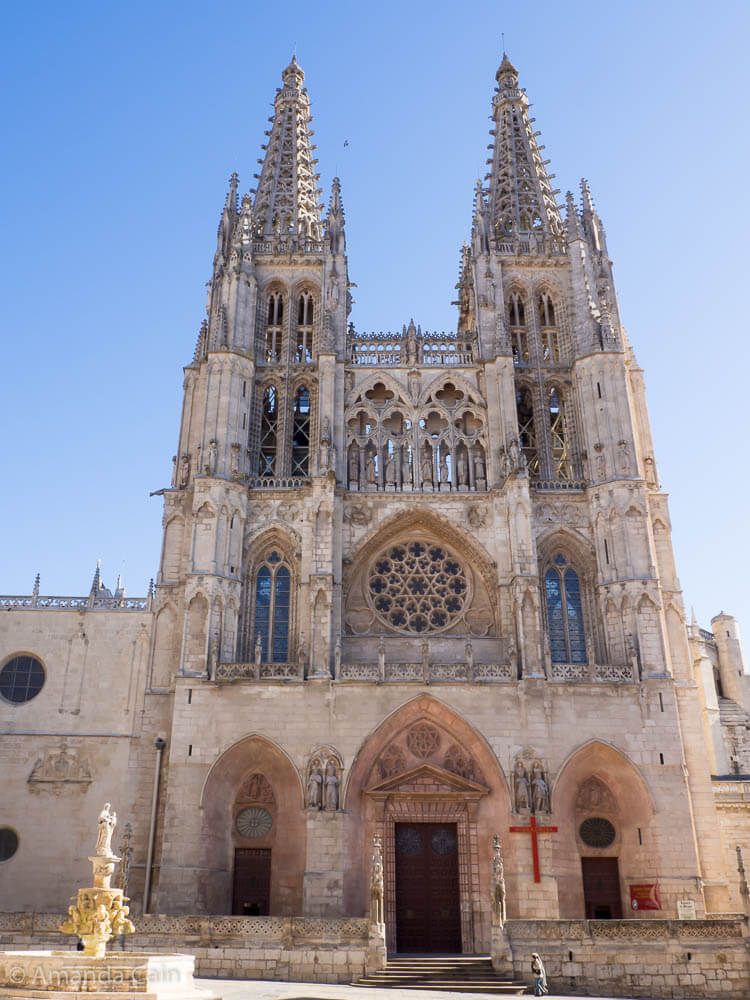 Two women enter Burgos Cathedral to pray.