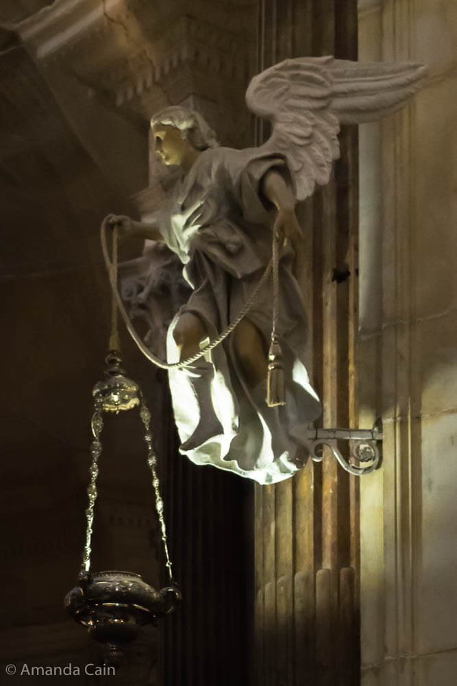 An angel in Cádiz Cathedral holding a lantern.