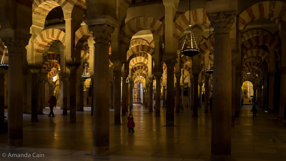 A small child lost in the endless forest of columns in Córdoba's Mezquita.