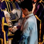 A young boy refills the incense burner in the Semana Santa procession.