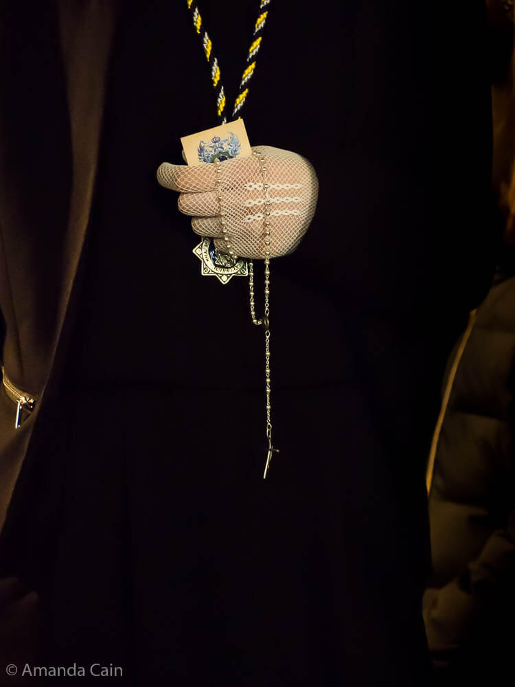 A woman marching in the Semana Santa procession clutches her holy objects close to her chest.