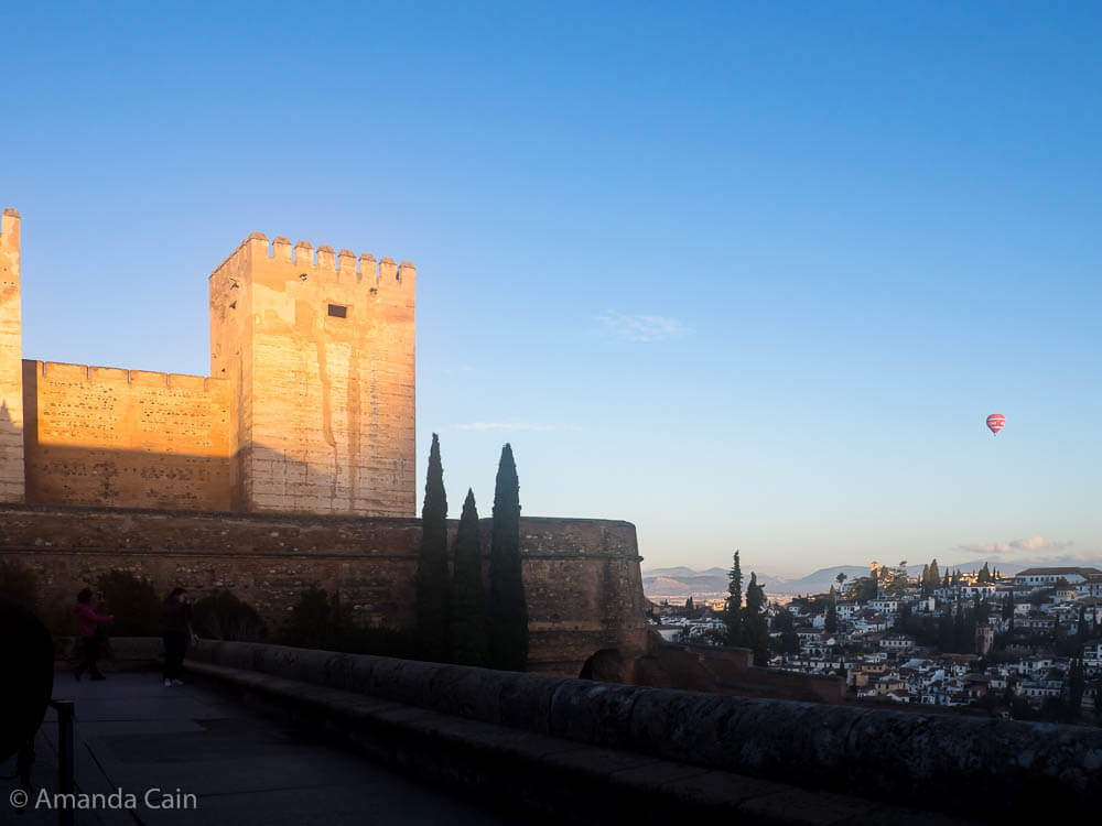 A picture of the Alhambra palace lit up with the dawn sunlight, with the houses of Granada in the background and a balloon making a dawn flight.
