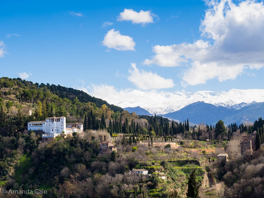 A picture of the Generalife and its gardens sitting on a hill with the snow-covered Sierra Nevada mountains in the background.