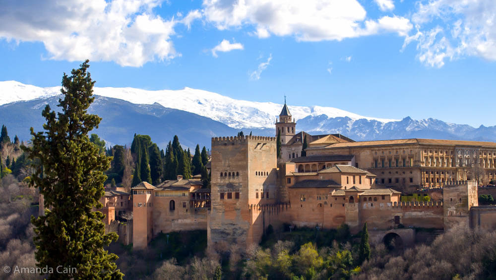 A picture of the Alhambra palace with it's fortifications, and the snow-covered Sierra Nevada mountains rising behind it.