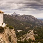 The belltower of Guadalest perched on top of a cliff with the valley running down to the sea, and dark storm clouds in sky above.