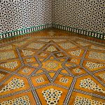 Intricate floor and wall tiling in Seville's Alcázar.