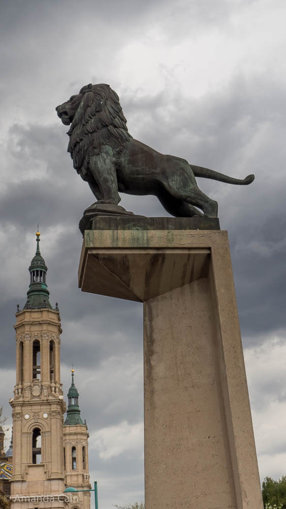 A bronze lion keeps watch over the city of Zaragoza.