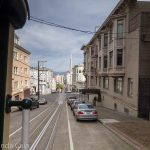 A picture of the view of San Francisco from a moving cable car.