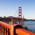 A picture of the Golden Gate Bridge with the red railing curving around in the foreground.