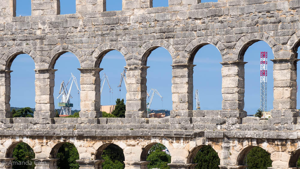 Old and new: the Ancient Roman amphitheatre and the modern port cranes of Pula.