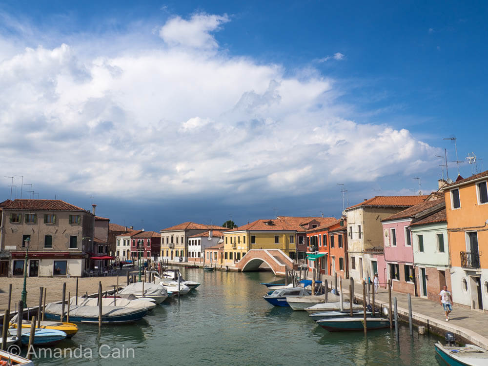 Storm clouds gather over a sunny Venetian canal.