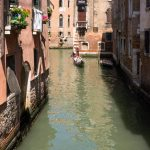 Tourists in a gondola exploring the small side canals of Venice.