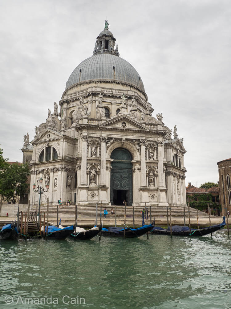 Gondolas parked outside of an extravagant church in Venice.
