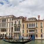 A typical scene in Venice; a gondola with tourists sailing down the Grand Canal.