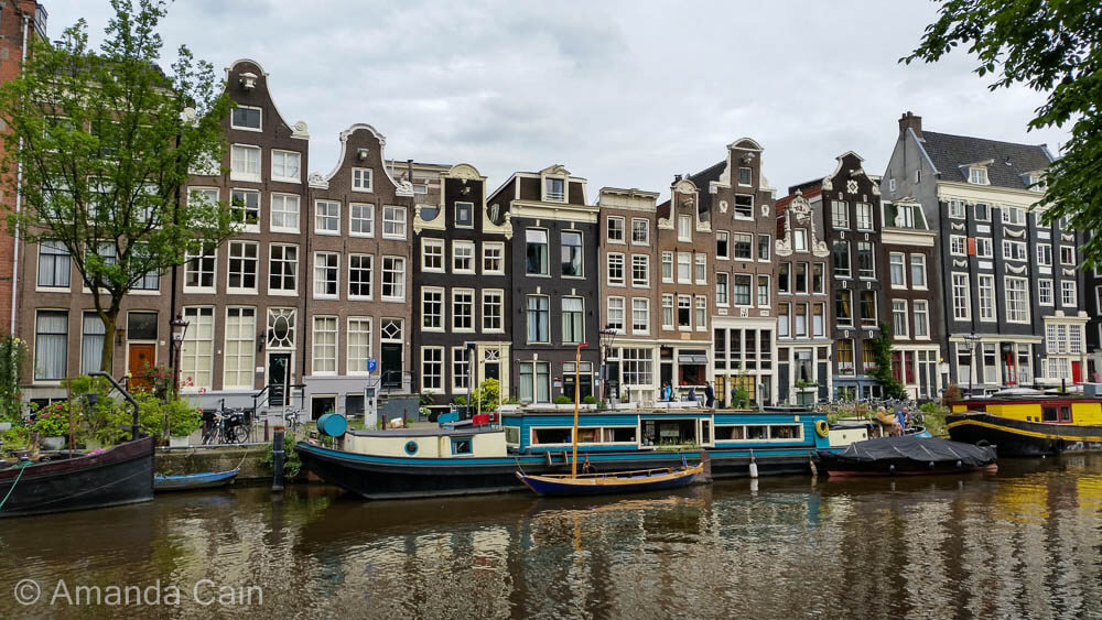 A typical Amsterdam canal with houseboats and canal houses.