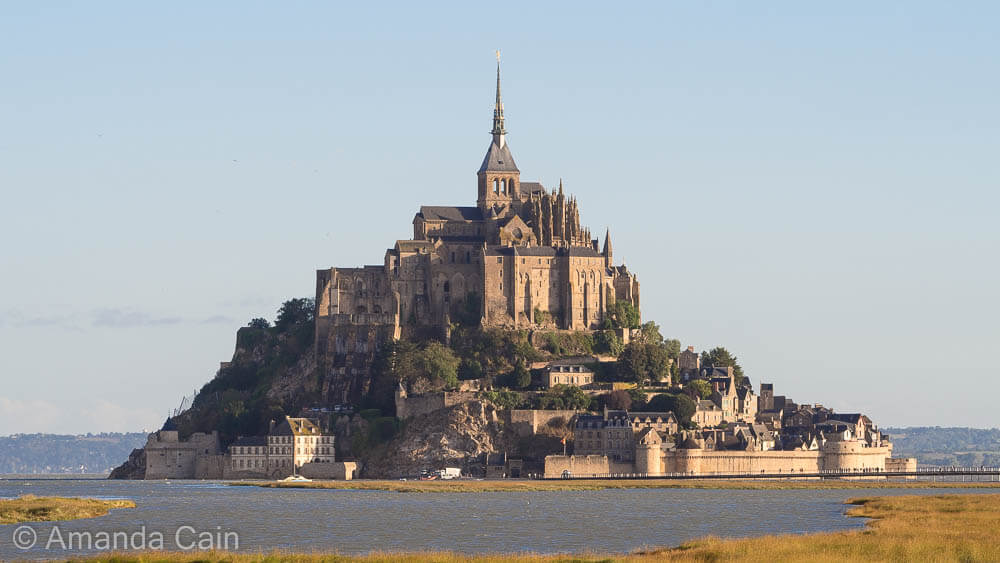 Mont Saint-Michel rising out of the bay at sunrise.