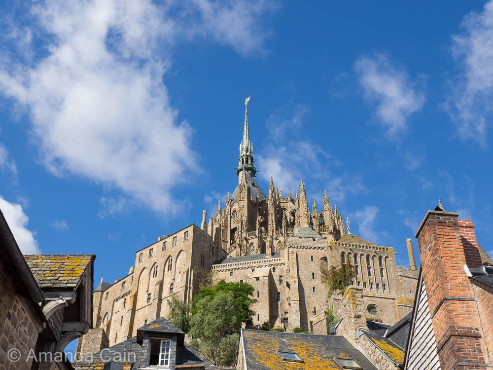 The fortified monastery of Mont Saint-Michel rising high above the buildings of the town.