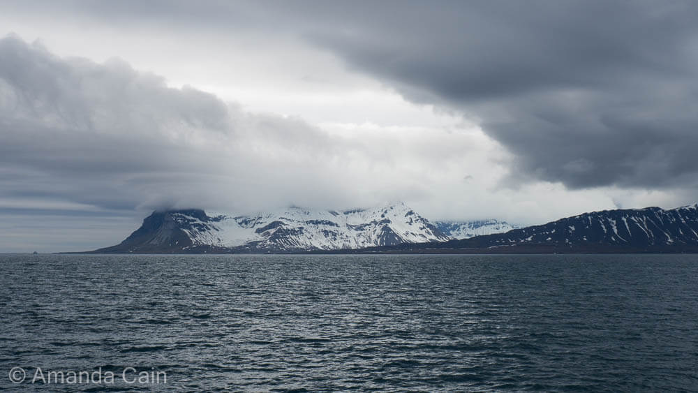 Mountains of Svalbard shrouded in clouds.