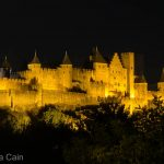 The fairy tale castle of Carcasonne lit up at night.