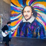 A busker in front of a newly painted Shakespeare mural.