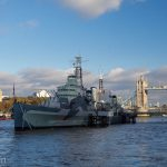 A modern warship against the old Tower of London and Tower Bridge.