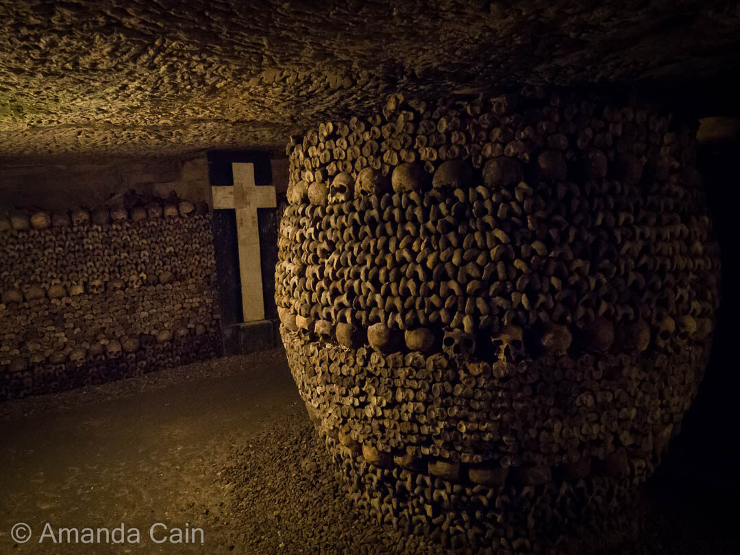 Inside the Catacombs of Paris, the bones of the long dead are arranged into various formations.