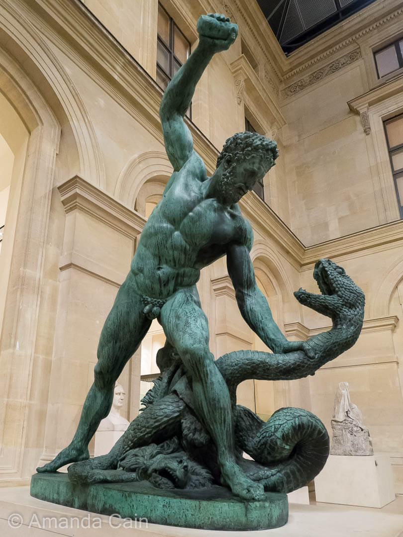 A bronze statue of Hercules fighting a snake, inside the Louvre Museum.