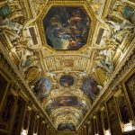 The richly decorated ceiling in the Apollo Gallery of the Louvre Museum.