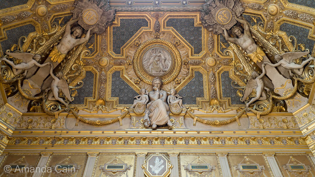 One of many richly decorated ceilings in the Louvre Museum.
