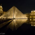 The glowing Main Pyramid of the Louvre reflected in the perfectly still fountain waters.