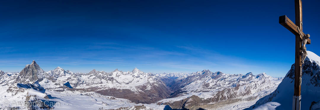 A panoramic view of the Swiss Alps with the Matterhorn on the far left, the town of Zermatt nestled in the valley in the centre, and the Breithorn on the right.