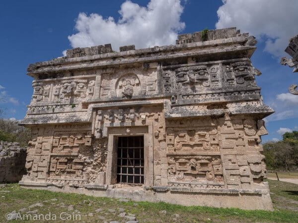 One of the richly decorated buildings in Chichen Itza. You can see faces on all the walls, the roof, and the side edges of the building.