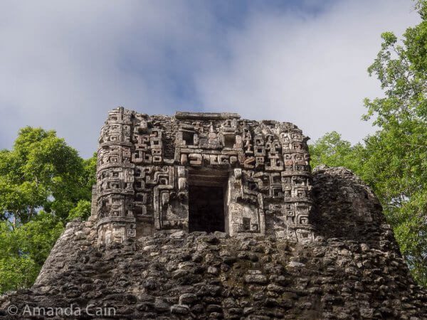 A highly decorated temple in Hormiguero. You can see a face above the door. The door is actually the mouth of the face, and it represents the portal to the underworld. You can also see smaller faces stacked along the side edges of the temple.