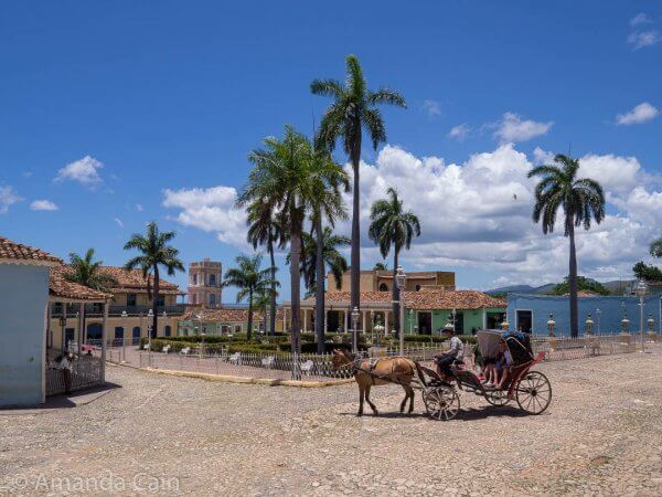 A horse and carriage passing through Trinidad's Plaza Mayor.