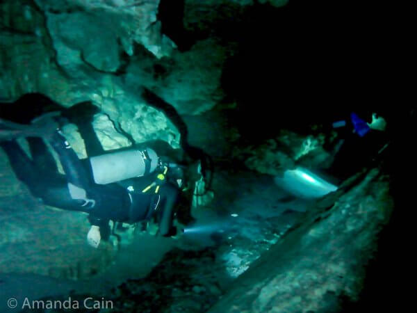 Pedr (left, facing right & holding a torch in his right hand) swimming through a narrow channel. Here you can see why they don't want beginner divers in this cenote: you need to be able to swim through without touching or brushing up against anything.
