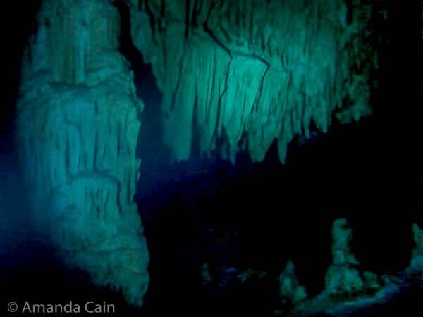 Limestone formations packed together, hanging from the ceiling & a large column on the left in the Bat Cave in Cenote Dos Ojos.