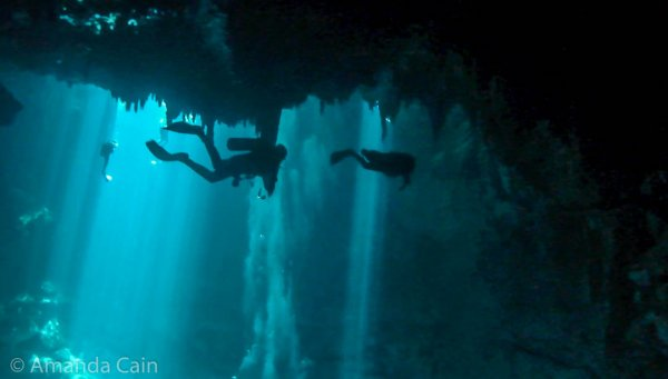 "Divers swimming below the ceiling (in the foreground), and bright shafts of ""laser lights"" streaming down from the cenote opening in the background."