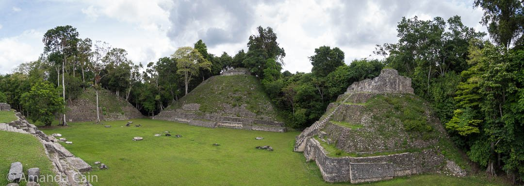 One of the large plazas in Caracol, surrounded by tall pyramid-temples that have only been partially restored.