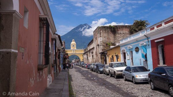 A street in Antigua with the Arch of Santa Catalina, and Volcan Agua rising up above everything.