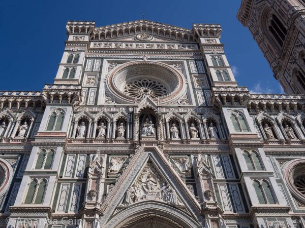 The front of Florence's Duomo: coverd in white, green and pink marble and statues of saints and apostles with Mary and Jesus in the middle.