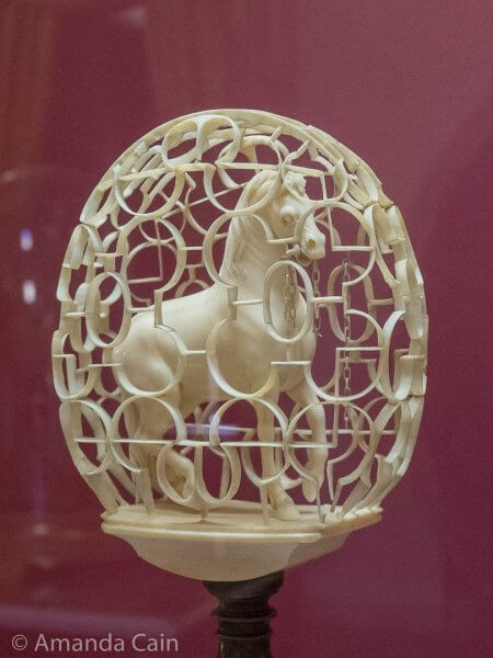 One of hundreds of delicately-carved ivory objects. This one is extra impressive because the horse, the chain, and the cage are all carved from a single piece of ivory.