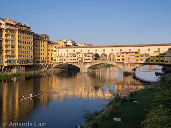Early morning rower on the Arno River, with the Ponte Vecchio bridge and its colourful shops lined up and sticking out over the sides.