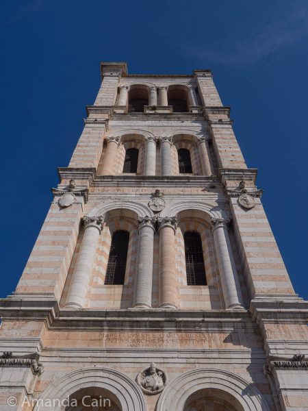 The pink and white striped marble tower of Ferrara's cathedral.